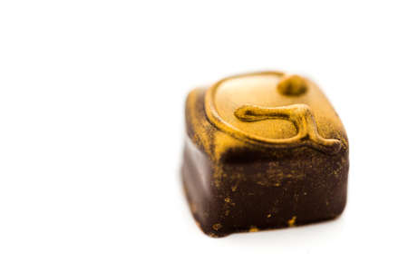 Gourmet ginger chocolate truffle on a white background.