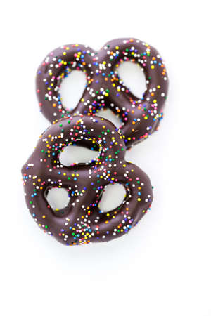 pretzel: Gourmet chocolate covered pretzel with Chocolate covered pretzel with multi colored sprinkles on a white background.