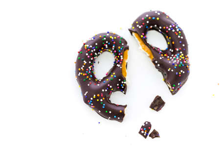 Gourmet chocolate covered pretzel with Chocolate covered pretzel with multi colored sprinkles on a white background.