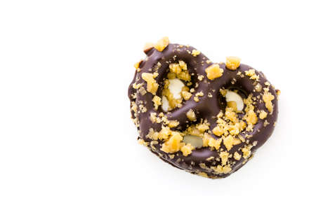 Gourmet chocolate covered pretzel with caramel chunks on a white background.