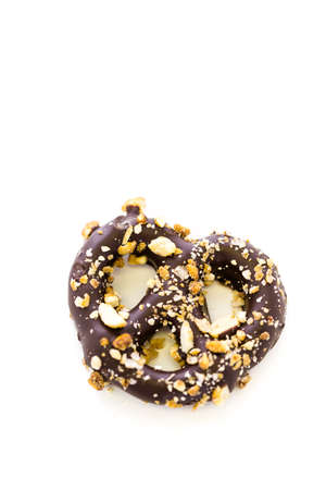 Gourmet chocolate covered pretzel with candy peanuts on a white background.
