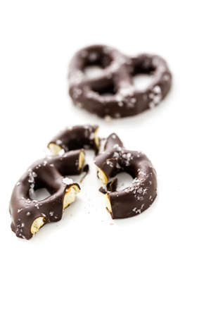 Gourmet chocolate covered pretzel with sea salt on a white background.