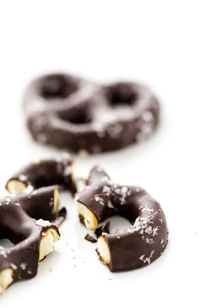 Gourmet chocolate covered pretzel with sea salt on a white background. photo