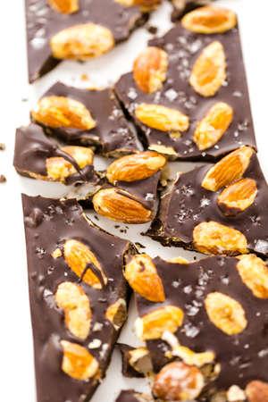almighty: Gourmet onnipotente barretta di cioccolato alle mandorle con sale marino su uno sfondo bianco. Archivio Fotografico