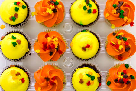 Miniature capcakes with yellow and orange icing and sprinkles.