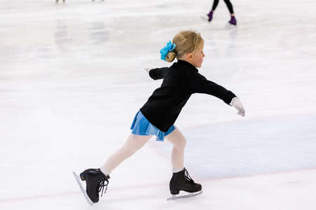 Cute young girl practicing figure skating on indoor ice skating rink. Archivio Fotografico