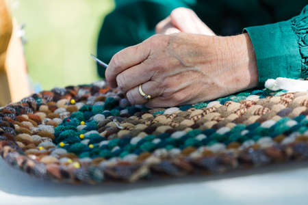Making a rug with vintage materials by old woman. Imagens