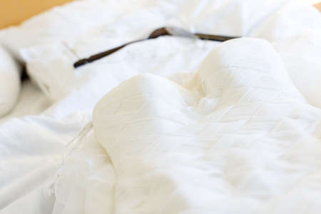 Wedding dress with hanger laying on the bed. Stock Photo