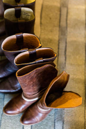 high priced: Cowboy boots of wedding party at fron tof fireplace.