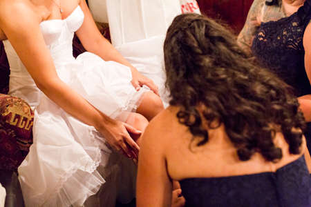 priced: Bride dressing up for her wedding dress with help of brides maids. Stock Photo