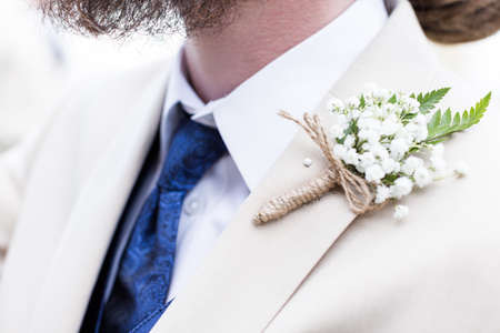 priced: Boutonniere pin up to grooms suit right before  wedding ceremony.
