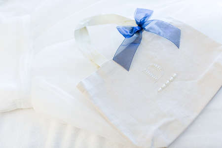 priced: White bag with blue bow for flower girl.