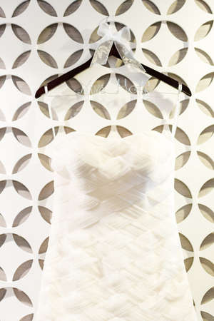 Wedding dress hanging on a white wall with pattern.
