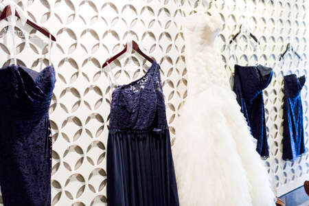priced: Wedding dress hanging on a white wall with pattern.