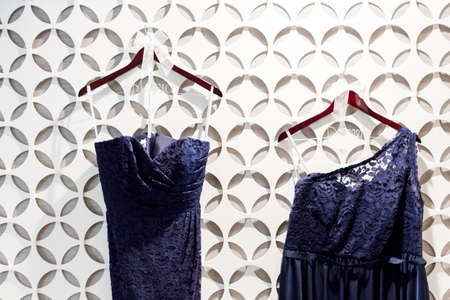 priced: Blue brides maids dresses hanging on a white wall with pattern.