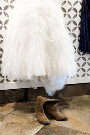 high priced: Wedding dress hanging on a white wall with pattern.