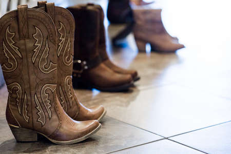 Cowboy boots of wedding party at fron tof fireplace.