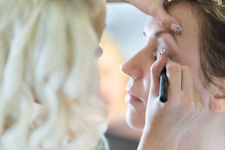 30 34 year old: Makeup artist applying make up to the brides face.