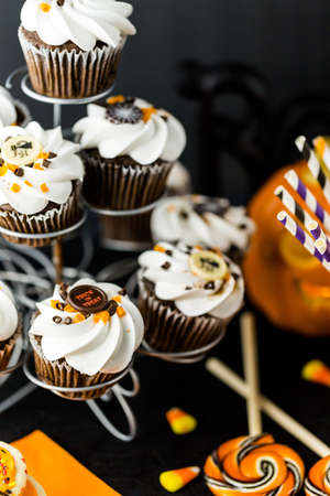 Chocolate Halloween cupcakes with white buttercreme icing and chocolate shavings on top.