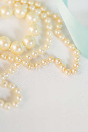 White vintage pearls on the table. Imagens