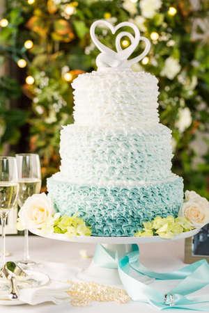 Gourmet con gradas de la torta de la boda como pieza central en la recepción de la boda. Foto de archivo