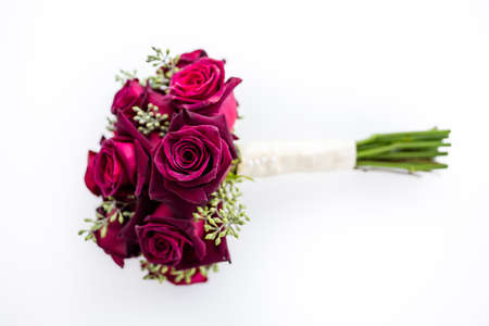 Small wedding bouquet with roses on a white .