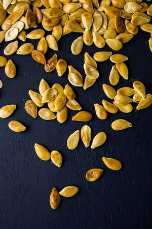 cucurbita: Home  cooked pumpkin seeds on black background.