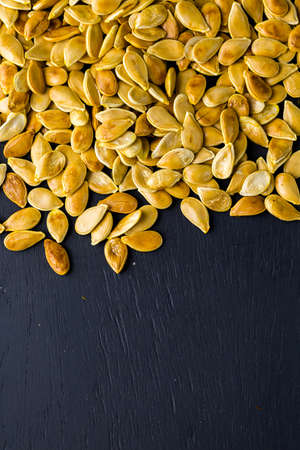 Home  cooked pumpkin seeds on black background.