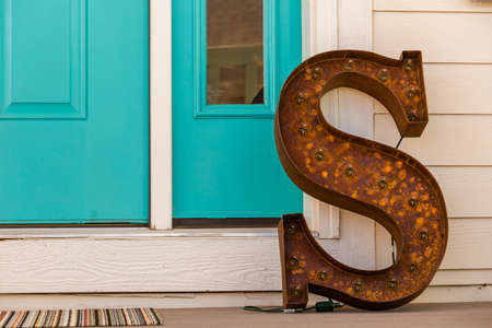 living unit: Large letter S made from rusted metal on the front poarch.