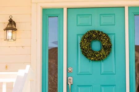 front door: Green wreath decorating front door.