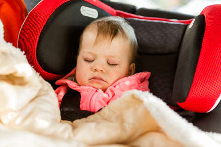 Cute baby girl sleeping in her car seat while traveling in the car.