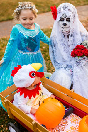 Trick or treating in costumes on Halloween night.