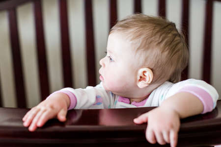 Cute baby girl standing in her crib.