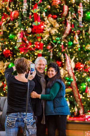 christmas in denver: Denver, Colorado, USA-November 23, 2014. Mature couple getting photographed at front of large Christmas tree.