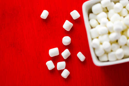 Small round white marshmallows on red backgrouns. Banco de Imagens