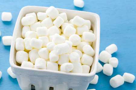 Small round white marshmallows on blue backgrouns. Banco de Imagens
