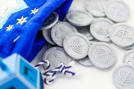 Blue dreidel with silver tokens on a white background Stock Photo