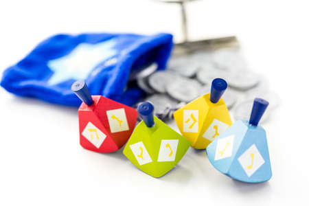hebrew alphabet: Colorful dreidels with silver tokens on a white background Stock Photo