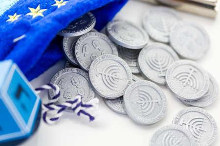 dreidel: Blue dreidel with silver tokens on a white background Stock Photo