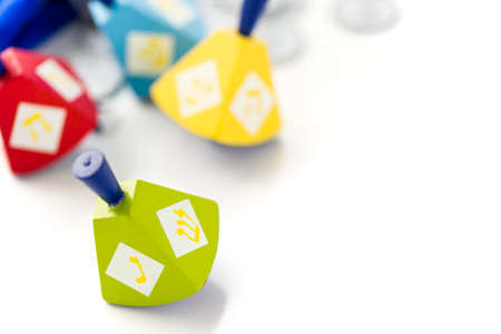 Colorful dreidels with silver tokens on a white background Stock Photo