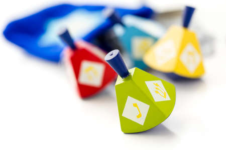 dreidels: Colorful dreidels with silver tokens on a white background Stock Photo