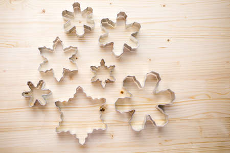wood cutter: Different size metal cookie cutters in shape of snow flakes. Stock Photo
