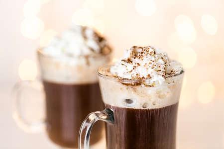 is hot: Chocolate caliente adornado con crema batida y el cacao en polvo. Foto de archivo
