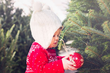 Cute baby girl in red Scandinavian dress at the Christmas tree farm. Stock Photo