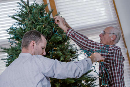 40 44 years: Family decorating beautiful live Christmas tree.