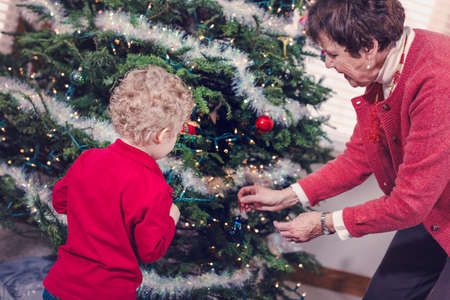 70 74 years: Family decorating beautiful live Christmas tree.