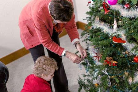 70 74 years: Family decorating beautiful live Christmas tree.