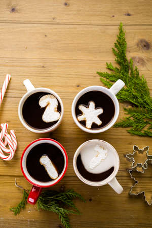 Cups with hot chocolate garnished with white marshmallows on wood table.