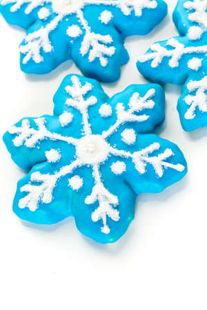 Frosted blue sugar cookies in shape of snowflakes.