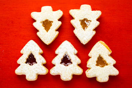 Linzer cookies in shape of Christmas tree on red background.